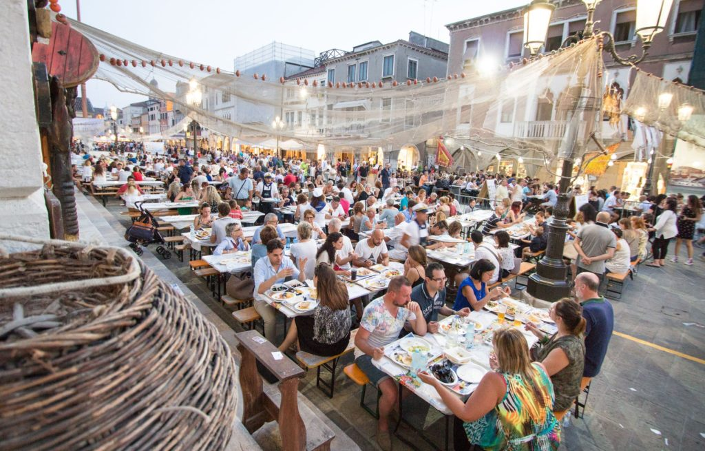 diners for dinner fish festival Chioggia Venice fishing nets